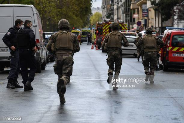 French soliders rush to the scene after several people were injured near the former offices of the French satirical magazine Charlie Hebdo following...