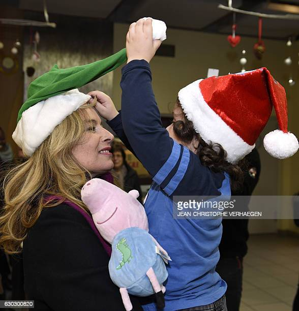 French sponsor of the movement 'Copains du monde' Valerie Trierweiler holds a child in her arms during a visit on December 20 2016 in Nilvange...