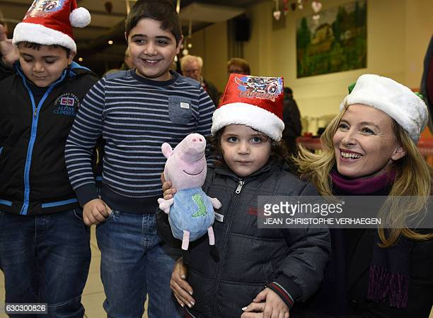 French sponsor of the movement 'Copains du monde' Valerie Trierweiler poses with children during a visit on December 20 2016 in Nilvange eastern...