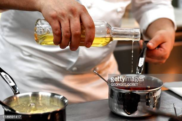 French starred chef Jerome Schilling, pours some Sauternes wine in a pan while cooking in the kitchens of the Lalique restaurant at Chateau...