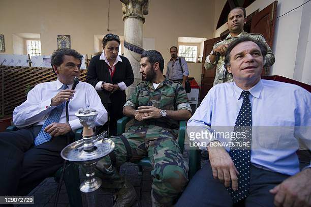 French State Minister for Foreign Trade Pierre Lellouche and Renaud Muselier smoke a shisha pipe in a coffee bar with a soldier loyal to the new...
