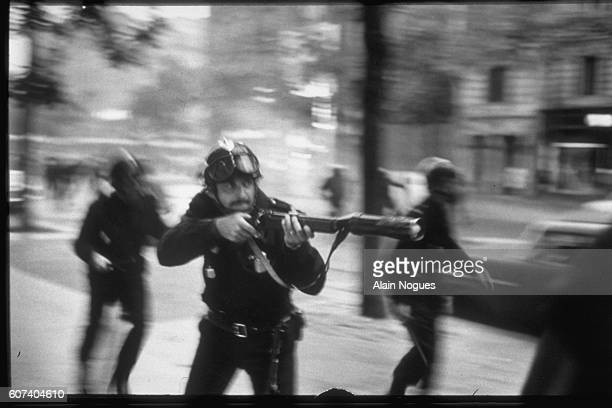 French state security police member launching a grenade on StGermain Boulevard during the Paris riots | Location StGermaindesPres Paris France