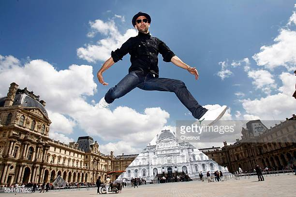 French street artist and photographer JR jumps in front of the Louvre museum on May 25 2016 in Paris France French street artist JR has installed a...