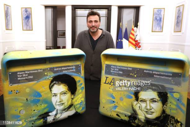 TOPSHOT French street artist Christian Guemy aka C215 poses next to mailboxes displaying a portrait of late French politician and Holocaust survivor...