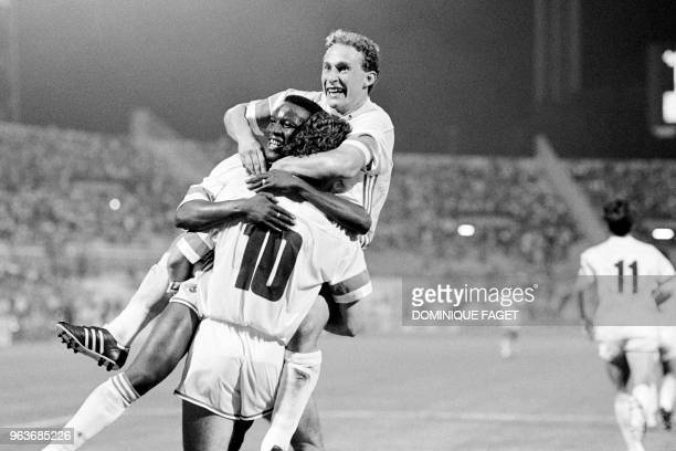 French striker JeanPierre Papin celebrates on August 7 1988 with forward Abdoulaye Diallo and midfielder Philippe Vercruysse after Olympique de...