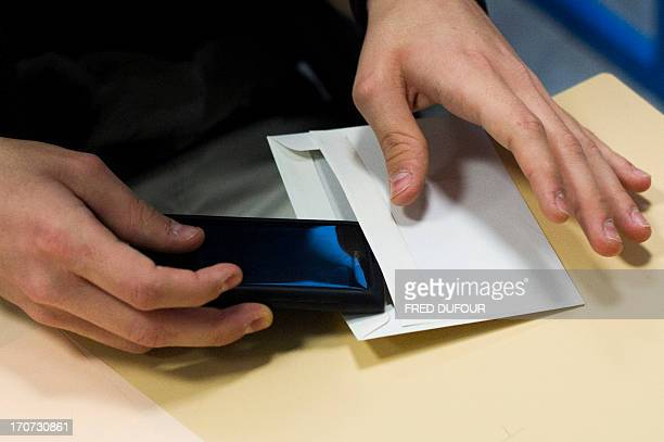 A French student puts his smartphone in an envelope to give it to supervisors before working on the test of philosophy as part of the baccalaureat...