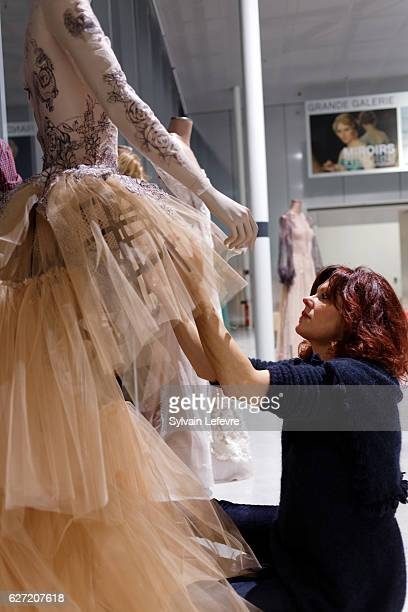 French stylist Sylvie Facon arranges the dresses and mannequins in the hall of the LouvreLens museum for the art exhibition and fashion show of...