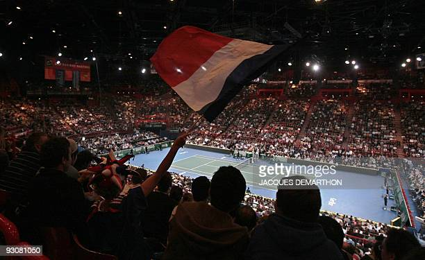 A French supporter waves a French flag ahead of the Paris Masters ATP tournament final tennis match between France's Gael Monfils and Serbian Novak...