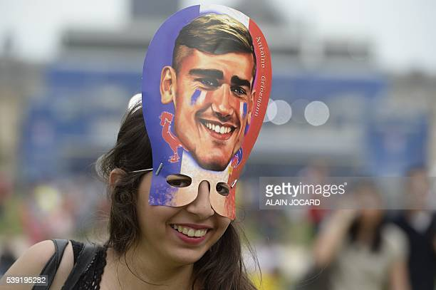 A French supporter wearing a mask representing French football team forward Antoine Griezmann smiles inside a fanzone ahead of the first football...