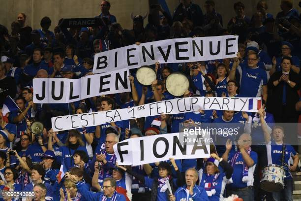 French supporters hold a banner reading 'Welcome Julien It's his first FedCup party' as they cheer their team during the FedCup World Group first...