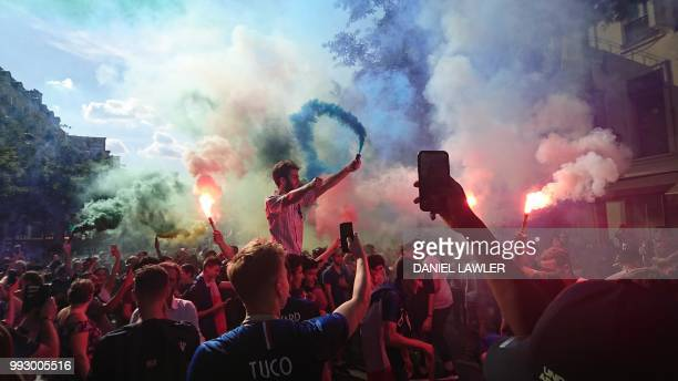 French supporters hold flares as they celebrate on Boulevard Poissonniere in Paris, on July 6 after France won the Russia 2018 World Cup...