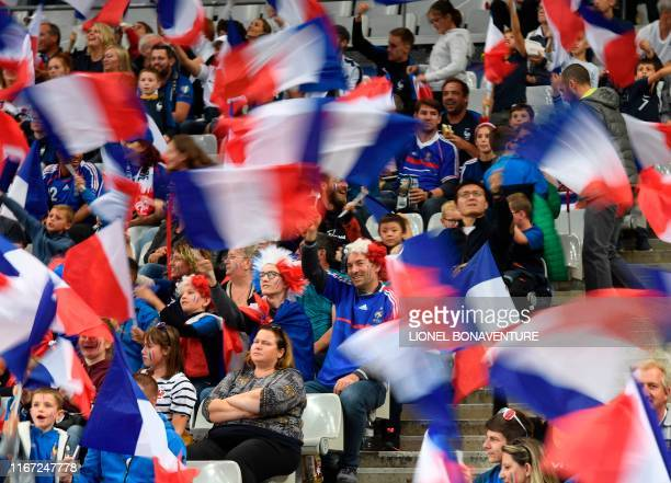 TOPSHOT French supporters wave flags and cheer prior to the kick off of the UEFA Euro 2020 qualifying Group H football match between France and...