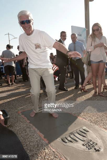 French surfer Joel De Rosnay leaves his footprint cement slab as he takes part in the inauguration of the Anglet Surf Avenue with other surfers from...