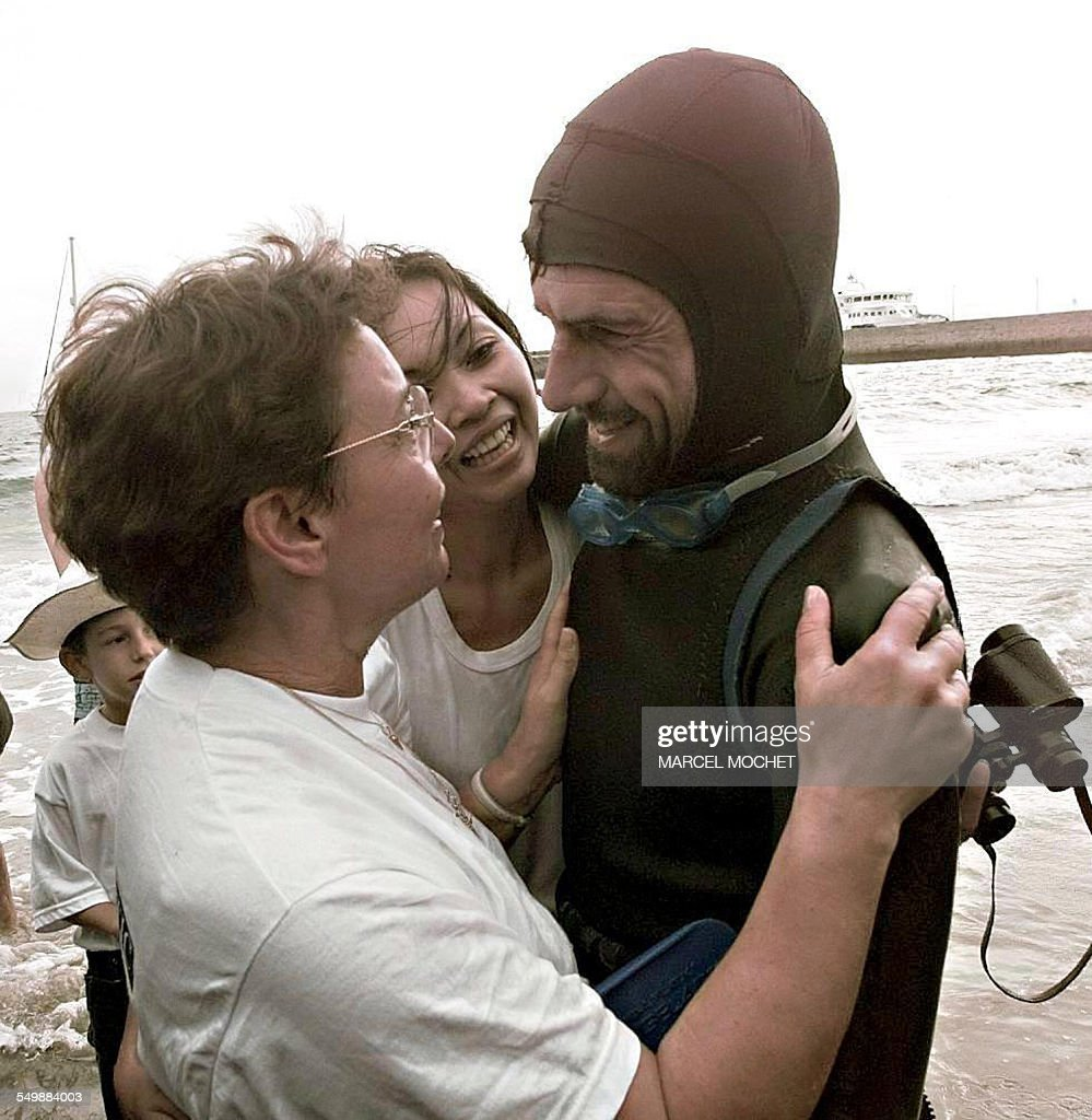 French swimmer Benoit 'Ben' Lecomte (R) is welcomed, on September 25, 1998 on the beach of Port-Maria in Quiberon by his girlfriend Tinny (C) and his mother Liliane (L), the arrival of his crossing the Atlantic from the United States to France. some 5,400 km, undertaken since mid-July.