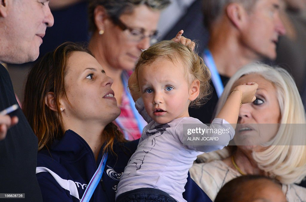 French swimmer Laure Manaudou (2ndL) holds her daughter Manon beside her mother-in-law and French swimmer Frederick Bousquet's mother (R) during the men's 4x50m medley relay final at the European Short Course Swimming Championships on November 22, 2012 in Chartres.