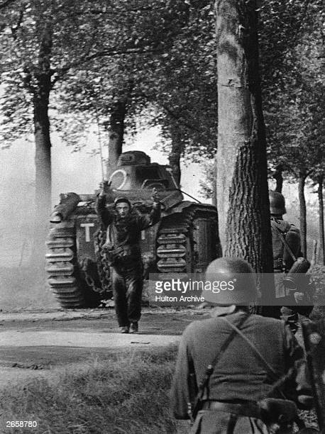 A French tank crewman surrenders to German armed forces during their rapid advance through western Europe using Blitzkrieg tactics