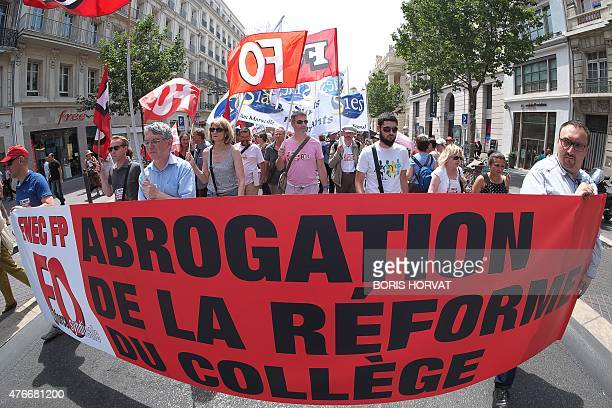 French teachers on strike hold labour union flags as they walk behind a banner which reads 'Remove the school reform' as they take part in a...