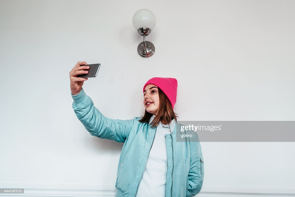 French teenage girl taking selfie in front of white wall for Creative selfie wall