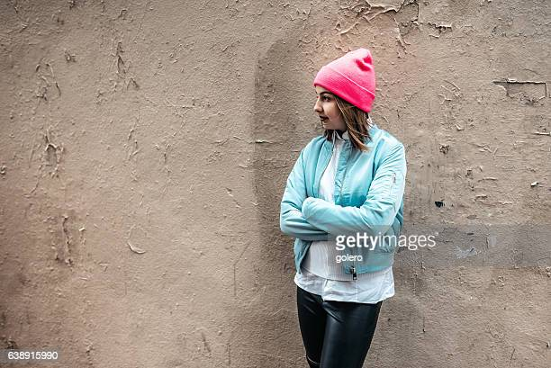 french teenage girl with bomber jacket and pink beanie outdoors