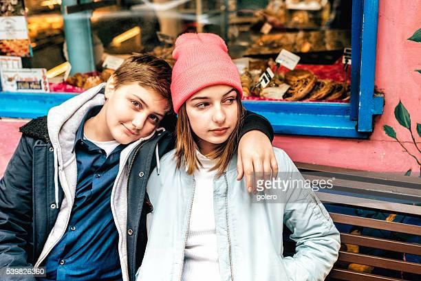 french teenage siblings on bench in Paris