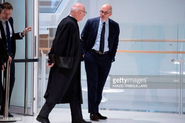 French telecom group Orange CEO Stephane Richard talks to a lawyer as he leaves after a suspension of the trial of French businessman Bernard Tapie...