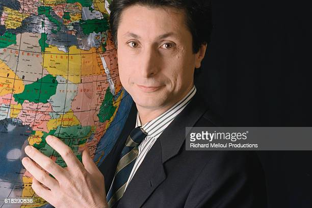 French television journalist Patrick de Carolis holds a plastic globe