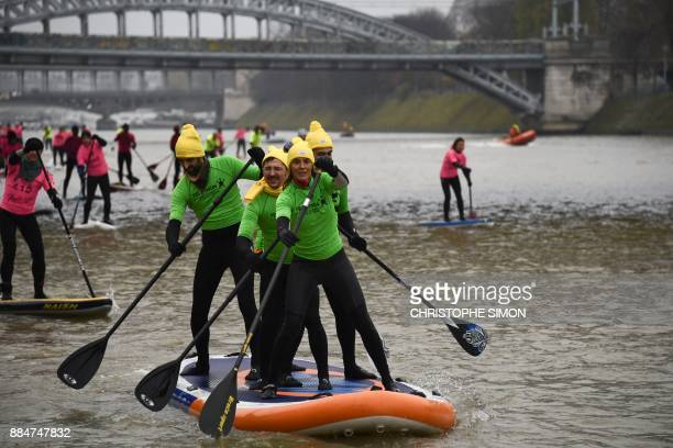 French television presenter Nathalie Simon and her team take part in the Nautic Sup Paris crossing stand up paddle race along the Seine River in...