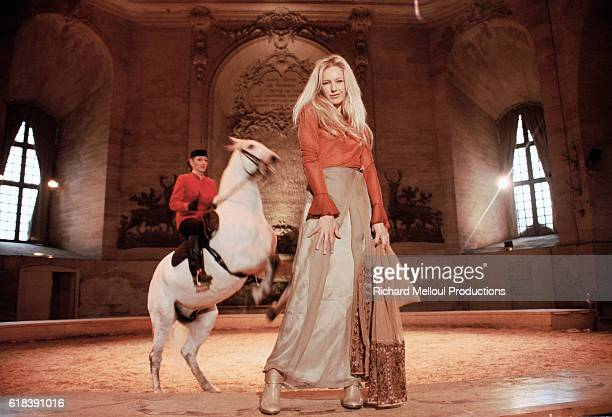 French television presenter Olivia Adriaco stands before a Lipizzan performing high school movements in an arena in Chantilly France