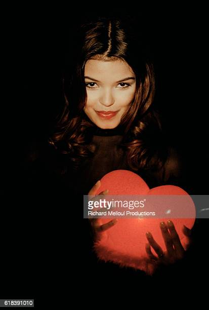 French television presenter Sandrine Ferrer holds a glowing heart