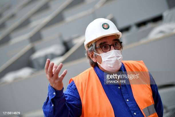 French Tennis Federation general director JeanFrancois Vilotte wears a protective facemask as he answers questions of a journalist during a visit to...