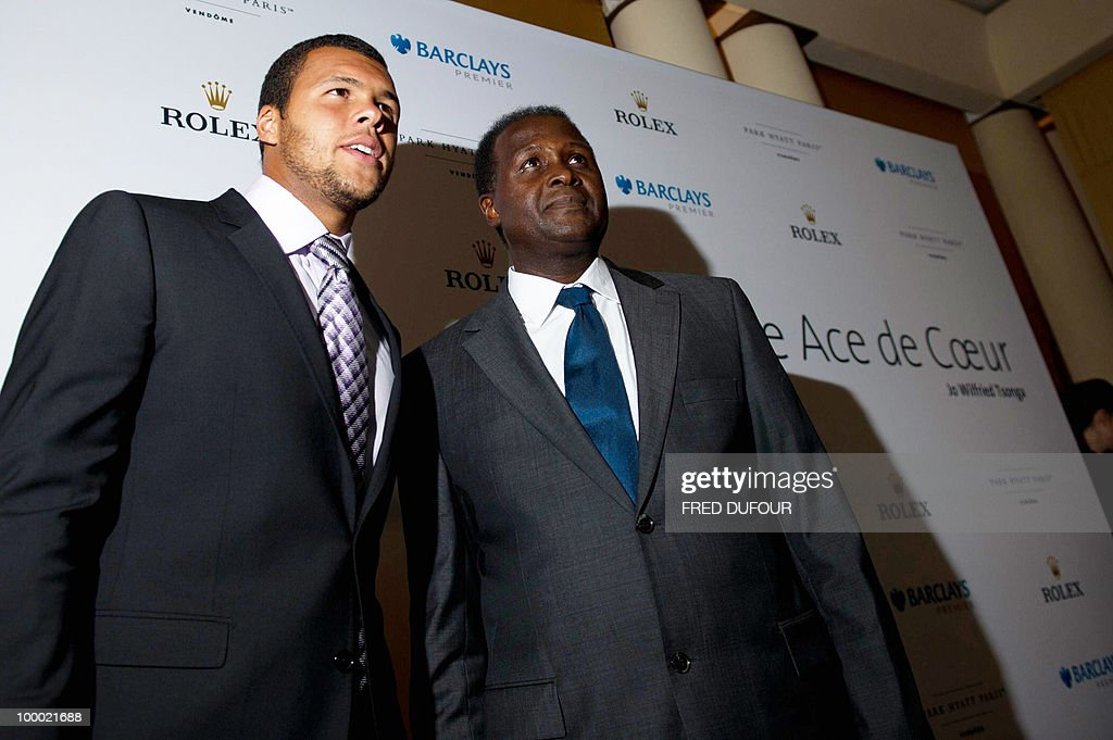 French tennis player Jo-Wilfrid Tsonga (L) poses with his father Didier Tsonga, on May 20, 2010, in a Paris hotel prior to a charity auction 'Ace de coeur' for 'Attrap'la balle' (Catch the ball) and 'Mecenat Chirurgie Cardiaque' (Cardiovascular surgery charity' French associations.