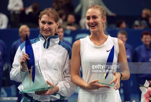 French tennis player Mary Pierce and German Steffi Graf hold their respectives trophies at the end of their Paris Indoor Open final the Open Gaz de...