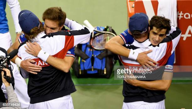 TOPSHOT French tennis player PierreHugues Herbert and Nicolas Mahut hug teammates after their victory over Japanese pair Yuichi Sugita and Yasutaka...