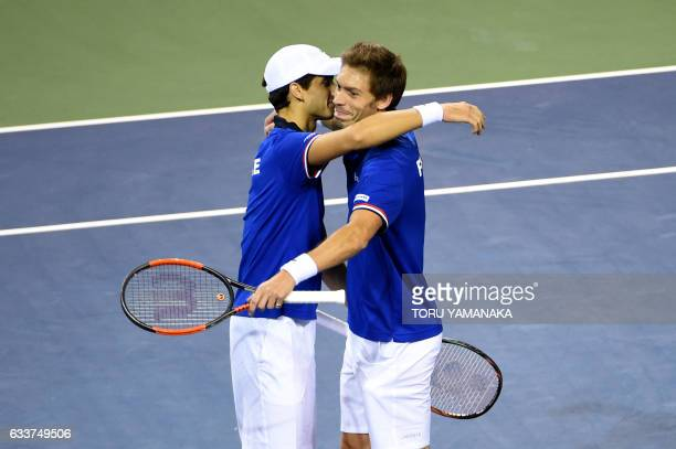TOPSHOT French tennis player PierreHugues Herbert hugs his partner Nicolas Mahut after their victory over Japanese pair Yuichi Sugita and Yasutaka...