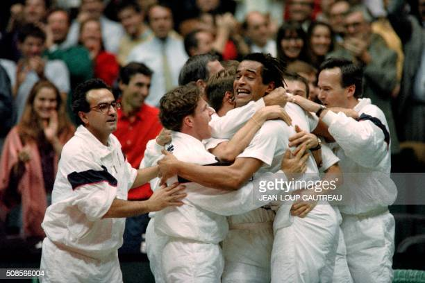 French tennis team captain Yannick Noah hugs his teammates after France defeated United States here 30 november 1991 in Lyon during the Davis Cup...