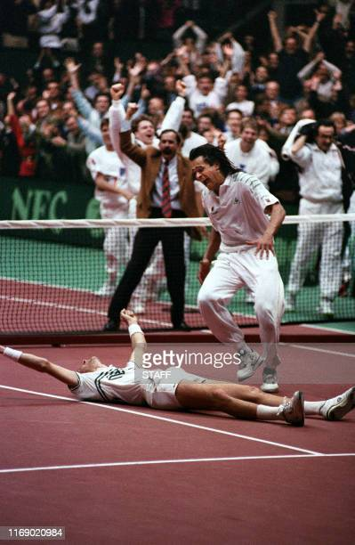 French Tennis Team Captain Yannick Noah runs to congratulate French Guy Forget after Forget defeated American Pete Sampras here 01 december 1991 in...