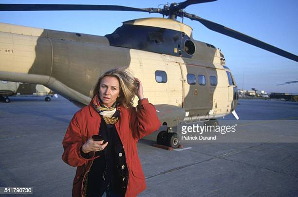 French TF1 journalist and globetrotter Marine Jacquemin in front of a helicopter