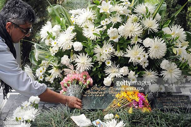 A French tourist puts flowers on the tombstone of Colombian drug lord Pablo Escobar at Montesacro cemetery on December 2 2010 in Medellin Antioquia...