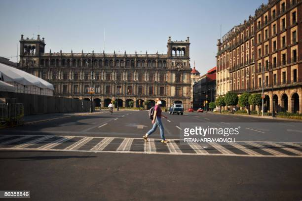 A French tourist wearing a face mask crosses an avenue in Mexico City's Zocalo on May 3 2009 The influenza A virus epidemic in Mexico is 'in phase of...