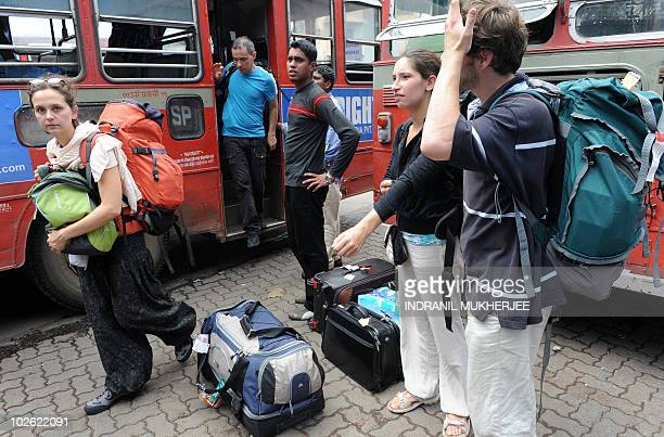 French tourists get off a bus to catch a train to their destination outside a city railway station during a strike in Mumbai on July 5 2010 Police...