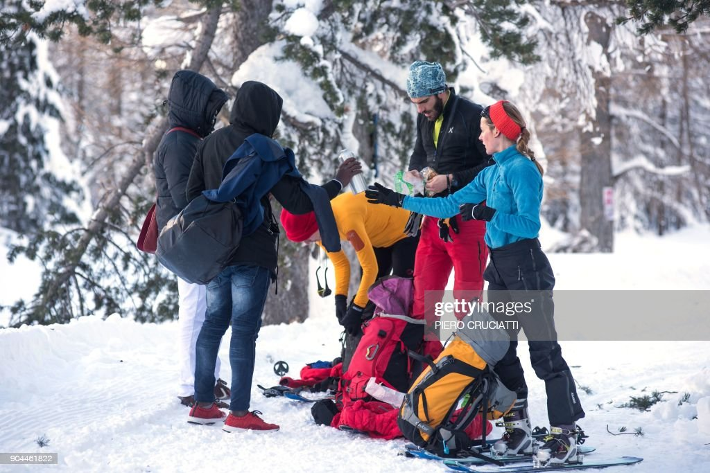 French tourists offer food and water to migrants from Ivory Coast walking in the snow on their way to the Colle della scala (Col de l'Echelle) a snow-covered pass to cross the border between Italy and France, on January 13, 2018 near Bardonecchia, Italian Alps. / AFP PHOTO / Piero CRUCIATTI