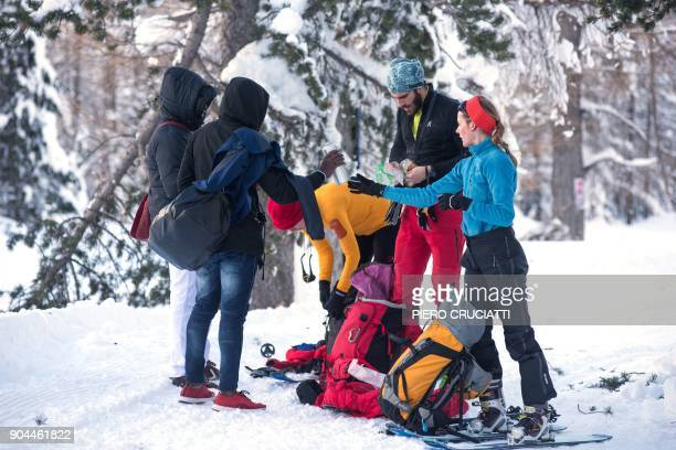 French tourists offer food and water to migrants from Ivory Coast walking in the snow on their way to the Colle della scala a snowcovered pass to...