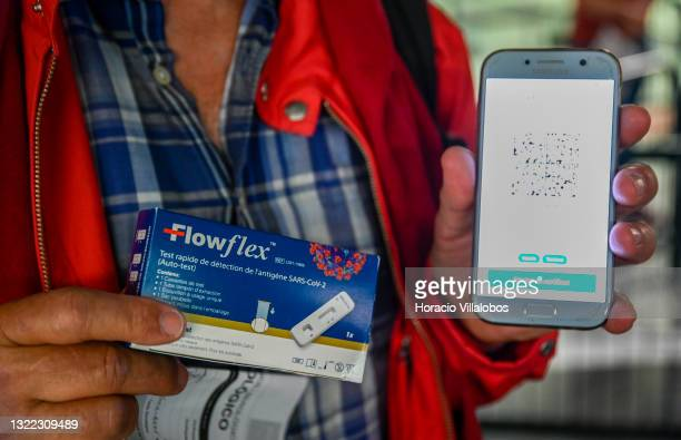 French traveler shows his Flowflex detection SARS-CoV-2 auto test and CR code of his French test, not accepted for flying, while queueing to be...