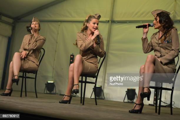 A French trio 'Girly Swing' dressed in US ARmy 1944 uniforms perform in front of crowd in Arromanches during DDay Festival Normandy 2017 Tuesday 6th...