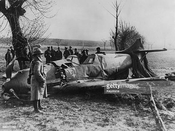 French troops guard the wreckage of a Messerschmitt BF 109E of Jagdgeschwader 54 of the German Luftwaffe and possibly flown by Oberleutnant Franz...