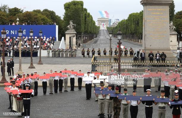 French troops members parade as the elite acrobatic flying team Patrouille de France performs a flying display of the French national flag over the...