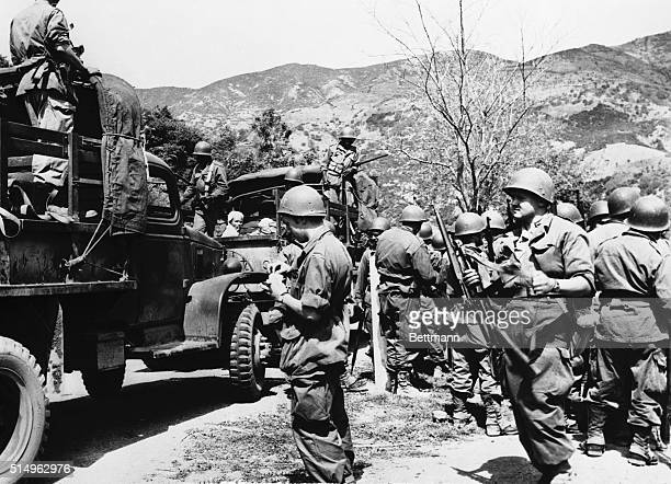 French troops mill about after loading trucks with Algerian Nationalist rebels captured in attacks following assaults by the rebels on military...