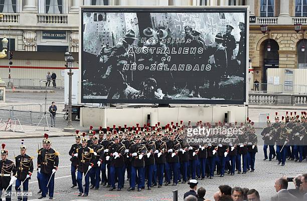 French troops of the detachment of honor of the Republican Guard walks past a screen reading Our allies from Australia and NewZealand before taking...