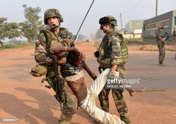 French troops of the Sangaris operation evacuate the body of a demonstrator who was shot dead near the international airport in Bangui on December...