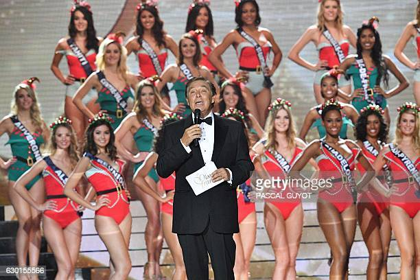 French TV host JeanPierre Foucault speaks as contestants appear on stage in swimsuit during the Miss France 2017 beauty contest on December 17 2016...